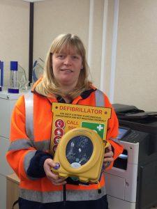Woman holding defibrillator