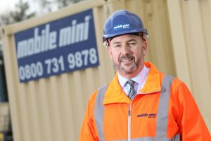 Chris Watcham stood in front of Mobile Mini storage container wearing safety hat and high visibility jacket
